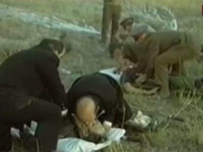 Άνδρες των σωστικών συνεργείων προσπαθούν να δώσουν τις πρώτες βοήθειες στα μέλη του πληρώματος του «Σογιούζ 11»