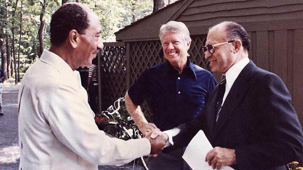 Οι Μπέγκιν και Σαντάτ σφίγγουν τα χέρια υπό το βλέμμα του Τζ. Κάρτερ