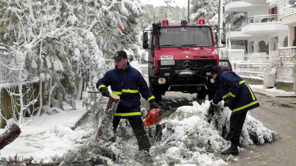 Πυροσβέστες κόβουν δέντρα που κατέρρευσαν από τις χιονοπτώσεις