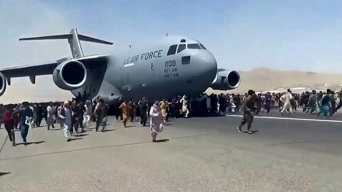 Απελπισμένοι Αφγανοί προσπαθούν να επιβιβαστούν σε μεταγωγικό της Πολεμικής Αεροπορίας των ΗΠΑ ενώ αυτό τροχοδρομεί στο αεροδρόμιο της Καμπούλ - Αύγουστος 2021